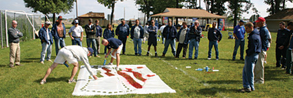 Pioneer salesmen at a Field Day demonstrating a stencil